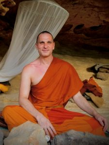 A person sitting in a cave smiling wearing orange robes.