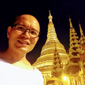 A person smiling standing in front of a buddhist temple