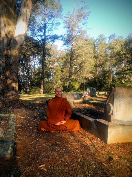 A Buddhist monk sits in meditation in an old cemetery.
