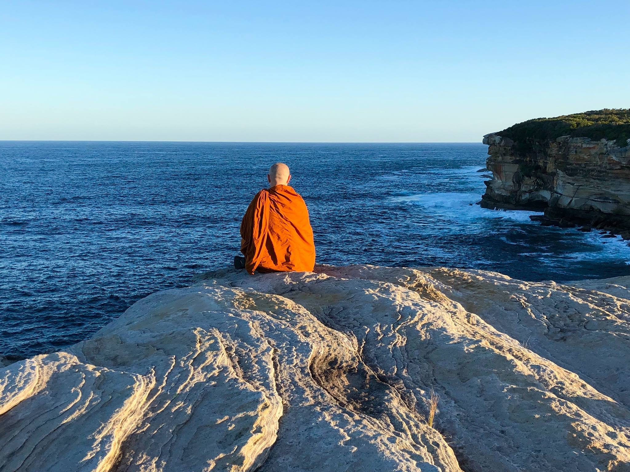 A Buddhist monk sits on a rocky cliff top looking out to the ocean, with horizon and blue sky.