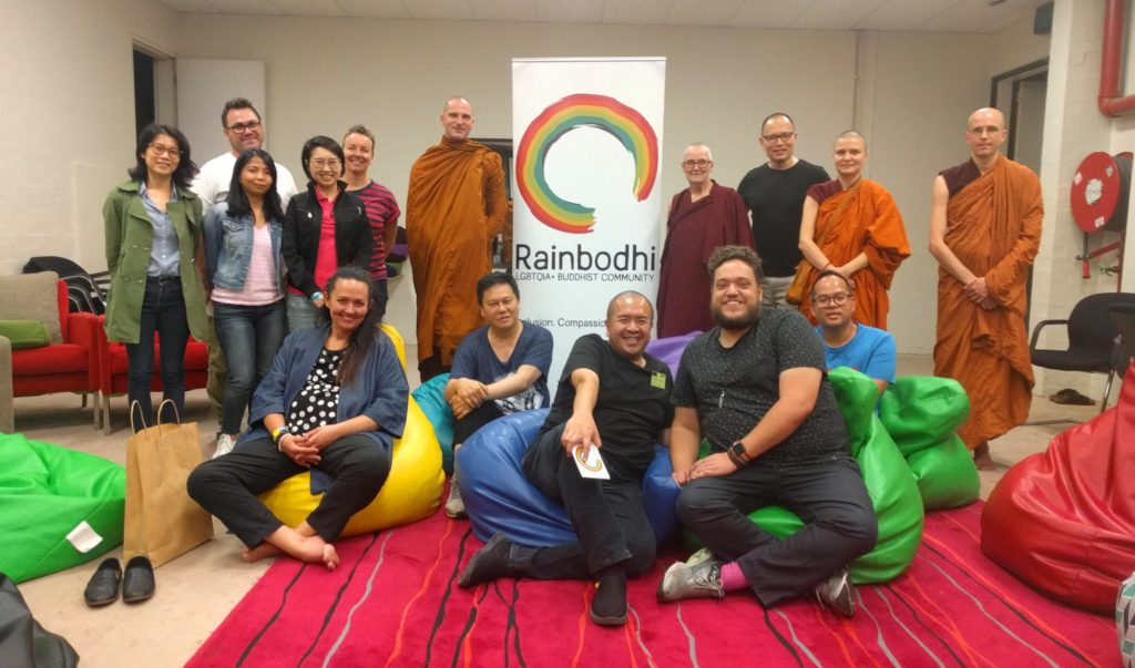 Group of people standing and sitting in frnt of the Rainbodhi banner, looking at the camera smiling