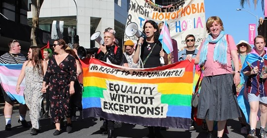 """Protesteors at a rally standing behind a banner that reads """"No discrimination, equality without excpetion"""""""